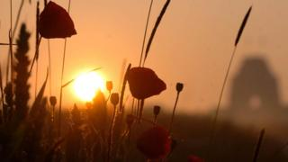 The sun rises over poppies in a field next to the Thiepval Memorial Monument in northern France which commemorates the Battle of the Somme.