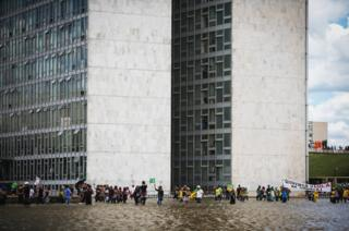 Anti-government demonstrators march through the water in front of the National Congress building