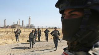 Iraqi forces walk in front of an oil production plant as they head towards the city of Kirkuk during an operation against Kurdish fighters on October 16, 2017