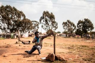 A protester uses a slingshot to hurl a stone at anti-riot police