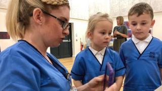 Schoolchildren in miniature uniforms