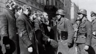 Nazi soldiers question Jews in Warsaw in 1943.
