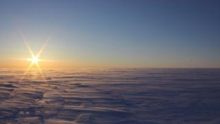 The sun over a windswept ice field