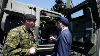 Defence Minister speaks to Corporal Huard after announcing Canada's new defence policy in Ottawa