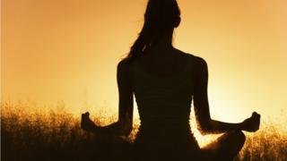 women meditating at sunset