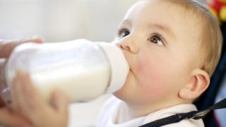 Baby drinking. Nine month old boy drinking a bottle of milk. feeding a baby.
