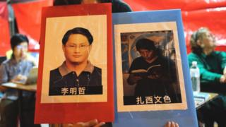 A volunteer holds placards of detained Taiwanese activist Lee Ming-cheh and Tibetan education advocate Tashi Wangchuk in Taipei on June 4, 2017