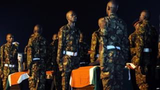Kenyan soldiers by the coffins of colleagues killed in Somalia
