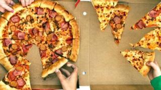 Unas personas tomando pedazos de una pizza