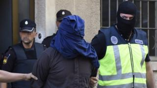 Policemen escort a suspect that was arrested as part of an international anti-jihadist police operation, in Palma Majorca on 28 June