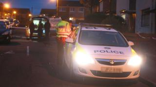 Police officers and vehicles at the scene of the incident in Newtownabbey