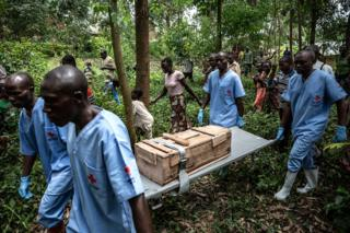 The Red Cross burial workers carry a box containing the body of an 11-month-old girl