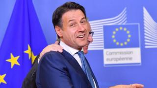 Italian Prime Minister Giuseppe Conte turns to the camera and laughs when led by the President of the European Commission Jean Claude Juncker