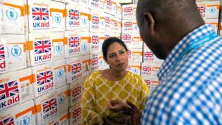 "Britain""s International Development Secretary Priti Patel speaks with a humanitarian aid agency worker in front of boxes of food aid at Mogadishu airport, Somalia June 17, 2017."