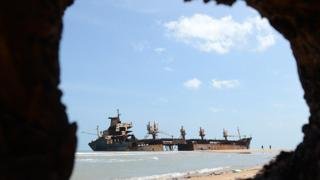 The wreckage of the Jordanian ship Farah-3, which ran aground after being captured by Tamil Tiger rebels in December 2006, is seen in the background as unseen Sri Lankan troops uncover a cache of weapons exposed by recent storm surges and heavy rains near the north-eastern town of Vellamullivaikkal in the Mullaittivu district on November 2, 2012. A storm surge in Sri Lanka's northeast has exposed buried artillery guns of Tamil Tiger rebels in a region where the final battles of the country's 37-year conflict were fought, the army said. Troops stumbled on four 152mm artillery barrels and one 130 mm piece believed to have been used by Tiger guerrillas during their last stand in the district of Mullaittivu, army spokesman Ruwan Wanigasooriya said. AFP PHOTO/ Ishara S. KODIKARA (Photo credit should read Ishara S.KODIKARA/AFP/Getty Images)