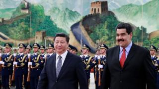 Xi Jinping e Maduro sorriem em cerimônia, aparecendo à frente de militares fardados e de uma grande pintura representando construções antigos em meio a paisagem chinesa