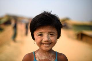 Rohingya refugee Nur Kayas, aged 6, poses for a photograph as she wears thanaka paste at Kutupalong camp in Cox's Bazaar, Bangladesh