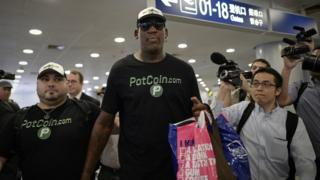 "Former NBA basketball player Dennis Rodman of the US gestures as he arrives to check-in for his flight to North Korea at Beijing""s international airport on June 13, 2017."