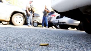 A spent cartridge lies on the ground as police officers secure the area after at least one person opened fire at a social services agency in San Bernardino, California December 2, 2015.
