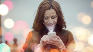 Phone scanning woman's face