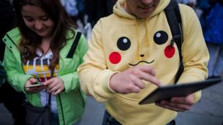Young people playing Pokemon Go with one dressed in a Pikachu hoodie