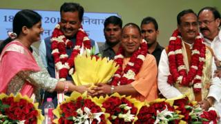Senior Leader of India's Bharatiya Janata Party (BJP) M. Venkaiah Naidu (R) Uttar Pradesh BJP Leaders Prasad Maurya (2L) and Dinesh Sharma (2R) look on as Yogi Adityanath (C) is presented with a floral bouquet during a ceremony in Lucknow on March 18, 2017, after he was picked as the new Chief Minister of the northern Indian state of Uttar Pradesh