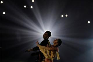 A male and female dancer perform together against a dark, dramatic backdrop