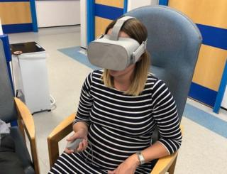 Pregnant woman sitting in a hospital chair wearing a VR headset