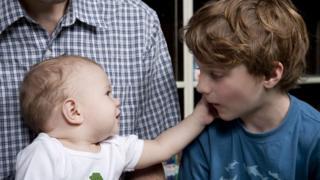 Un bebé acaricia la cara de un niño durante el programa.