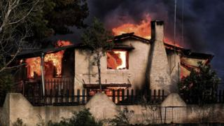 A house burns during a wildfire in Kineta, near Athens, on 23 July 2018