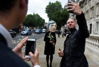 A man takes a selfie with the protester wearing a Theresa May mask the day after Britain's election