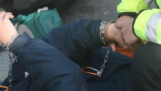 Protester being handcuffed near Heathrow Airport