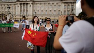 Chinese tourists have their pictures taken outside Buckingham Palace on July 29, 2012 in London, England