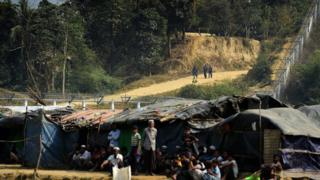 Myanmar security personnel keeps watch along the Myanmar-Bangladesh border as Rohingya refugee sit outside their makeshifts shelters near Tombru