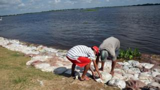 Locals set up sand bags to prevent the waters to reach the city of Alberdi, 130 km south of Asuncion on December 30, 2015