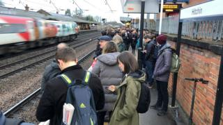 People waiting on a crowded platform at Hitchin station, where commuters were hit by early morning cancellations and delays after a freight train derailed.