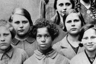 """Esta foto fue usada en conferencias sobre genética de la Academia Nacional para la Raza y la Salud, en Dresden, Alemania, 1936. Título original: """"niña mulata de una mujer alemana y un negro de las tropas de al Renania francesa, entre sus compañeros de clase alemanes""""."""