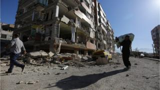 伊朗萨波勒—扎哈布镇居民走过一座地震中倒塌楼房(13/11/2017)