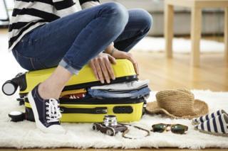Женщина, сидящая на желтом чемодане в попытке его закрыть