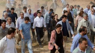 The leader of Turkey's main pro-Kurdish HDP Selahattin Demirtas (C in white shirt) and his delegation cross through a field after the road leading to Cizre was blocked by the Turkish security forces in Sirnak (9 Sept 2015)