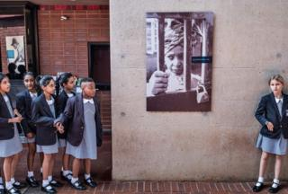 South African school children pause next to a portrait of the late South African anti-apartheid campaigner Winnie Madikizela-Mandela at her house in Soweto - 3 April 2018
