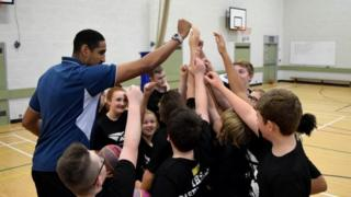 Glasgow Rocks' Kieron Achara with young basketball players