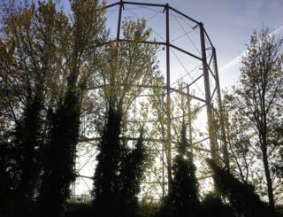 A steel structure behind trees