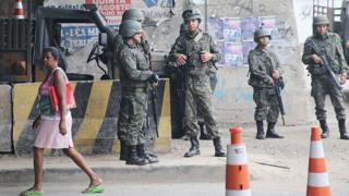 Mulher passa por militares na Maré, em 2014