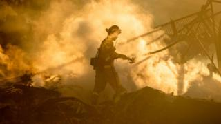 in_pictures A firefighter sprays down the smouldering remains of a home during the Hillside Fire in the North Park near San Bernardino, California