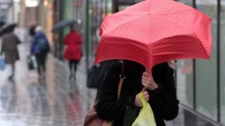 A shopper with a red umbrella