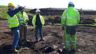 Archaeologists standing round cist