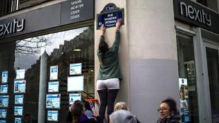 "An activist renames a street with a sticker reading ""Wonder Woman Street"" during a so-called ""Feminist Strike"" demonstration on International Women's Day in Paris, France,"