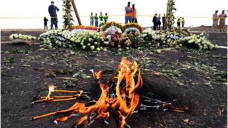 Candles burn during a commemoration ceremony for the victims at the scene of the Ethiopian Airlines Flight 302 plane crash, near Addis Ababa, Ethiopia