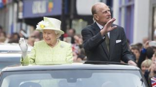 The Queen and Prince Philip waving at wellwishers